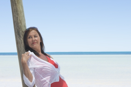 sexy mature women: Portrait attractive mature woman on holiday leaning relaxed  at wooden pole, with tropical ocean and blue sky as blurred background and copy space. Stock Photo