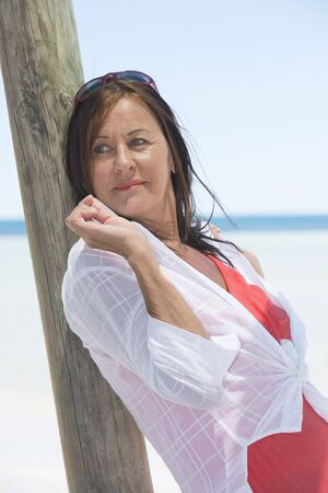 sexy mature women: Portrait attractive mature woman on holiday leaning relaxed  at wooden pole, with tropical ocean, horizon and blue sky as blurred background.