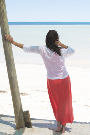 mature brunette: Attractive mature woman on holiday vacation at tropical beach, overlooking ocean to horizon and blue sky as blurred background.