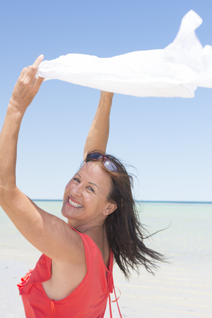 sexy mature women: Portrait beautiful happy mature woman at tropical beach holiday, holding  white cloth in wind, with horizon, ocean and blue sky as blurred background.