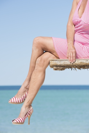 woman sandals: Beautiful legs of mature woman sitting in sexy pose on wood plattform above the ocean, wearing summer dress and high heels, overlooking the tropical sea, with horizon and blue sky as background and copy space.