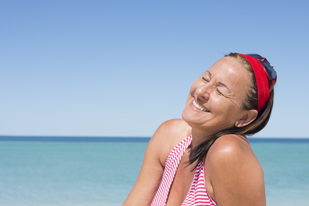 beack: Portrait attractive happy mature woman smiling joyful, relaxed with closed eyes, enjoying active lifestyle and retirement at beack holiday vacation, with ocean and blue sky as background and copy space.