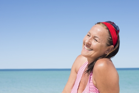relaxed woman: Portrait attractive happy mature woman smiling joyful, relaxed, enjoying active lifestyle and retirement at beack holiday vacation, with ocean and blue sky as background and copy space. Stock Photo