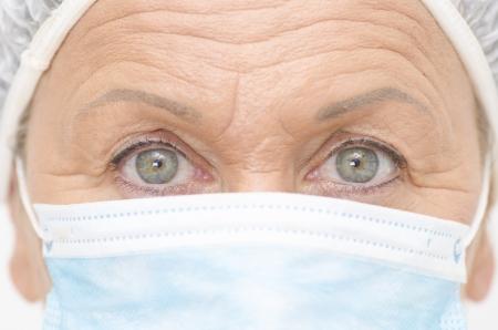 enfermera con cofia: Cerrar un retrato de la enfermera médica, con máscara, gorro y hermoso ojos y arrugas