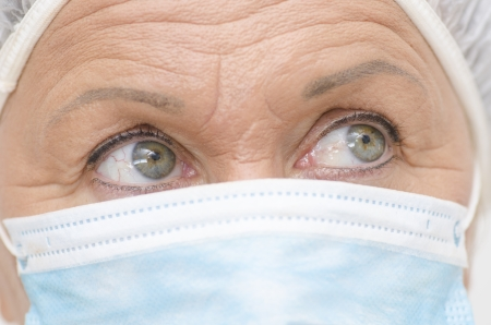 Close up portrait of female medical nurse, with mask, cap and beautiful eyes and wrinkles  photo