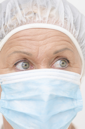Close up portrait of female hospital medical nurse, with mask, cap and beautiful eyes and wrinkles  photo