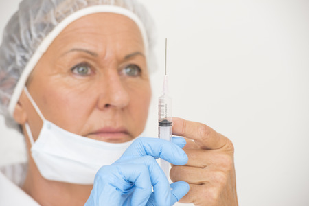 Portrait serious professional female hospital nurse in blurred background with syringe in hand with blue glove, isolated on white and copy space  photo