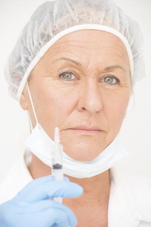 needle syringe infection: Portrait serious professional female hospital nurse with blurred syringe, vaccine injection, isolated on white