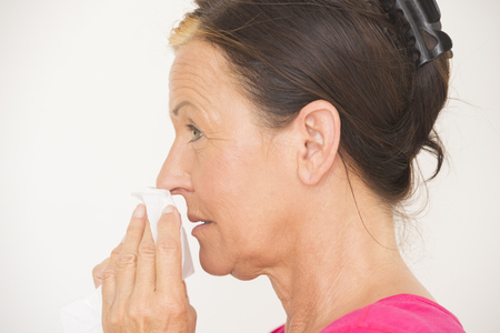 running nose: Portrait attractive mature woman with tissue in hands to clean running nose, suffering from flu, cold or allergy, isolated on white.