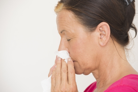 running nose: Portrait attractive senior woman with tissue in hands to clean running nose, suffering from flu, cold or allergy, isolated on white.