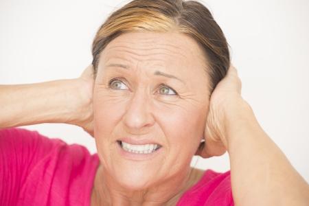 Ritratto stressata e preoccupata donna matura con le mani sulla testa, sulle orecchie, isolati su bianco. Archivio Fotografico