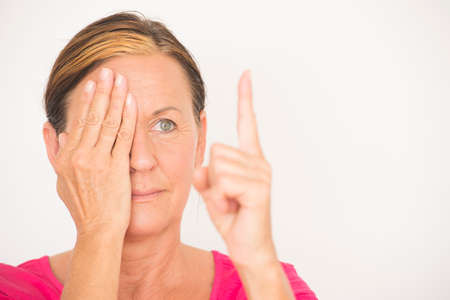 eyesight: Portrait attractive mature woman, covering one eye with hand and focusing on finger in blurred foreground, testing eyesight, isolated on white with copy space.