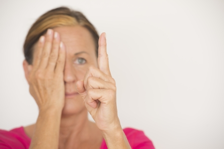 Portrait attractive mature woman in blurred background, covering one eye with hand and focusing on finger in foreground, testing eyesight, isolated on white with copy space. photo