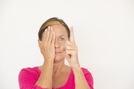 Portrait attractive mature woman covering one eye with hand and focusing on finger, testing eyesight, friendly face, isolated on white with copy space. photo