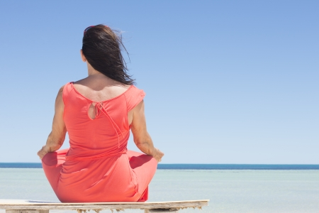 Portrait attractive mature woman in red summer dress sitting relaxed meditating at beach, enjoying tropical holiday vacation, looking over ocean, with horizon and blue sky as background and copy space. photo