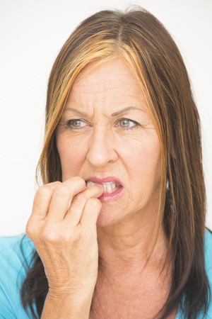 biting: Portrait attractive but nervous and anxious looking mature woman, biting fingernails, with worried and stressed facial expression, isolated on white. Stock Photo