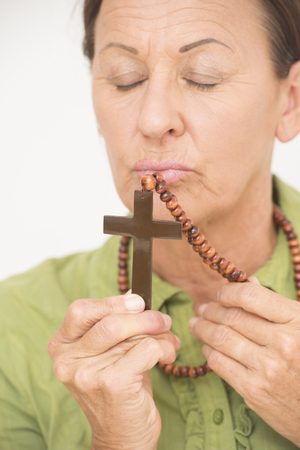 Portrait mature religious woman worshipping and kissing christian crucifix. photo