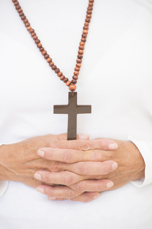 Closeup of praying female hands religious symbol of crucifix and rosary necklace. photo