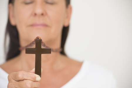 crucifix: Portrait woman in blurred background holding christian symbol of crucifix in hand. Stock Photo