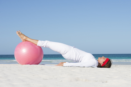 Relaxed attractive senior woman exercising with gymnastic ball at beach. photo