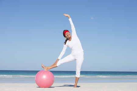 Fit and healthy attractive mature woman happy exercising with gymnastic ball at beach. Stock Photo