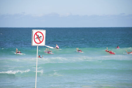 no swimming sign: No swimming sign in the sharp foreground at beach. Stock Photo
