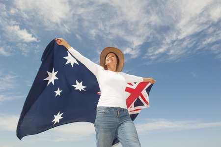 Attractive mature woman wearing akubra hat and with Australian flag around shoulder, isolated with blue sky  and clouds as background and copy space.