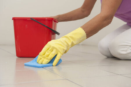 slippery: Hand in yellow rubber glove cleaning floor tiles with sponge, with woman, housewife in blurred background and copy space. Stock Photo
