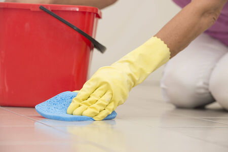 mopped: Close up Hand in yellow rubber glove cleaning floor tiles with sponge, with woman, housewife in blurred background and copy space.