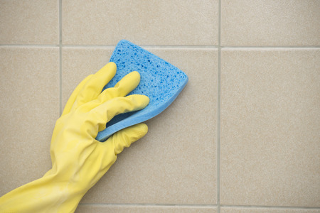 Hand in yellow rubber glove cleaning tiles with blue sponge, copy space. photo