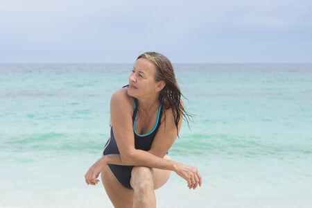 bathers: Ritratto bella cercando sportiva donna matura in bagnanti in spiaggia, posa rilassato e fiducioso, con l'oceano, l'orizzonte e il cielo come sfondo sfocato.