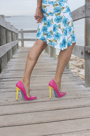 Woman balancing in very high heel shoes on boardwalk at beach, with ocean and sky as blurred background.