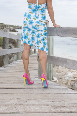Woman with attractive legs, wearing summer dress and high heel shoes, standing alone on boardwalk at beach, with coast and ocean as blurred background.