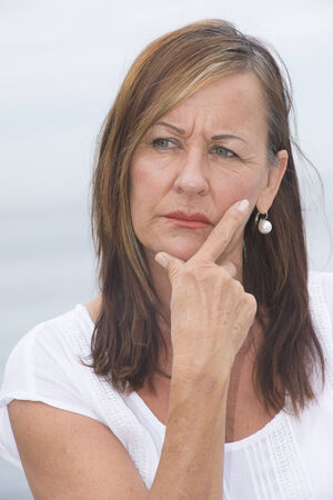Portrait attractive mature woman looking concerned and worried, thoughtful with hand on cheek.