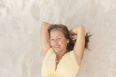 Portrait happy attractive mature woman lying relaxed smiling on sand at beach looking upward into camera, enjoying leisure time, copy space. photo