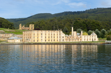 gaol: former Penal Convict Settlement Port Arthur on Tasmania, Australia, with ruin of prison at water of harbour and other old buildings.