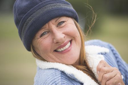 mujer sola: Retrato confidente feliz sonriente atractiva mujer madura al aire libre, el uso de cap� caliente y una chaqueta de lana, fondo verde borrosa.