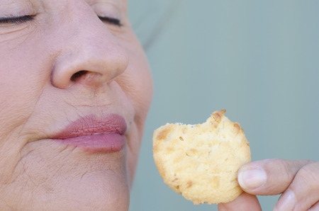close up eyes: Close up portrait of mature woman enjoying eating cookie as sweet snack, closed eyes.