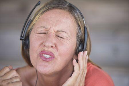 ojos cerrados: Retrato atractiva mujer madura escuchando y cantando feliz relajada con los ojos cerrados a la m�sica con auriculares, fondo borroso.