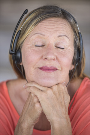 laid back: Portrait attractive mature woman listening happy relaxed with closed eyes to music with headphones, blurred background. Stock Photo