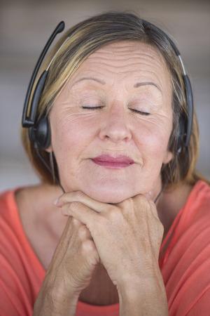 ojos cerrados: Retrato atractiva mujer madura escuchando feliz relajada con los ojos cerrados a la m�sica con auriculares, fondo borroso.