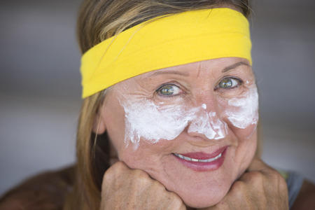 moisturiser: Portrait sporty fit active attractive mature woman with protective sunscreen skin care creme and moisturiser lotion on happy smiling face, yellow headband, blurred background.