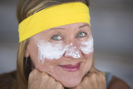 moisturiser: Portrait fit active attractive mature woman with protective sunscreen skin care creme and moisturiser lotion on happy smiling face, yellow headband, blurred background.