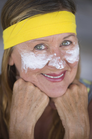 moisturiser: Portrait sporty active attractive mature woman with protective sunscreen skin care creme and moisturiser lotion on happy smiling face, yellow headband, blurred background. Stock Photo