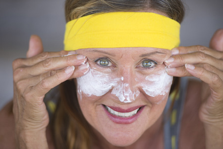 moisturiser: Portrait sporty fit attractive mature woman with protective sunscreen skin care creme and moisturiser lotion on happy smiling face, yellow headband, blurred background.
