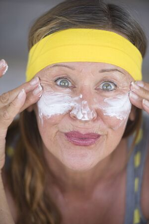 moisturiser: Portrait sporty fit active attractive mature woman with protective sunscreen skin care creme and moisturiser lotion on joyful smiling face yellow headband blurred background.