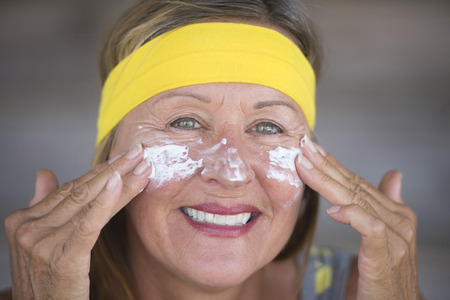 moisturiser: Portrait fit active attractive mature woman with protective sunscreen skin care creme and moisturiser lotion on joyful smiling face, yellow headband, blurred background. Stock Photo
