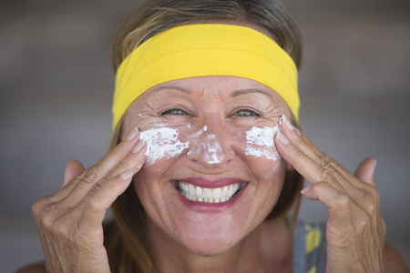 moisturiser: Portrait sporty active attractive mature woman with protective sunscreen skin care creme and moisturiser lotion on joyful smiling face, yellow headband, blurred background. Stock Photo