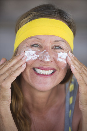 moisturiser: Portrait sporty fit active attractive mature woman, protective sunscreen skin care creme and moisturiser lotion on happy smiling face, yellow headband, blurred background. Stock Photo