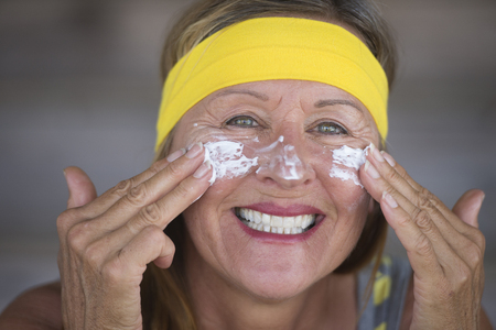moisturiser: Portrait sporty fit active attractive mature woman with sunscreen skin care creme and moisturiser lotion on joyful smiling face, yellow headband, blurred background.